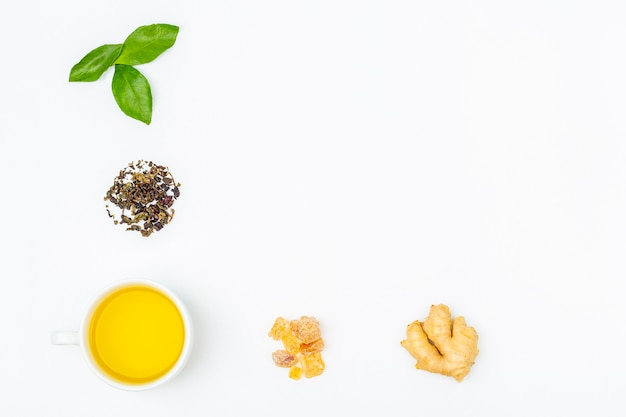 Layout of cup of oolong tea with fresh leaves, heap dry green tea, candy sugar and ginger root on white background, copy space for text. organic herbal, green asian tea for the tea ceremony. flat lay