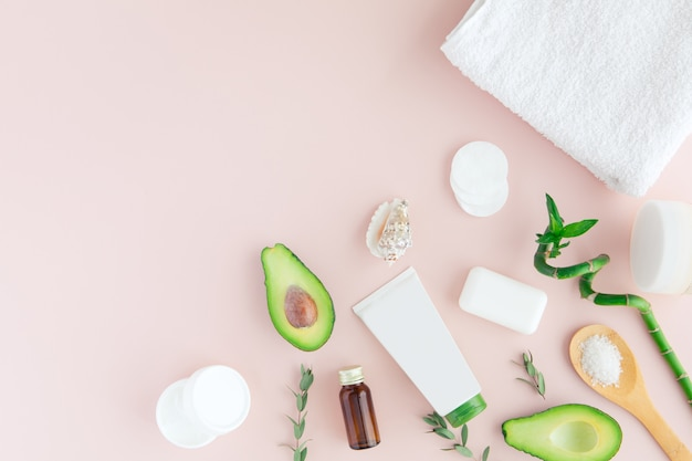 Layout of green white pink spa and wellness frame with towel, bamboo, tropical leaves , avocado, bottle of oil, body and face care tools on pastel.