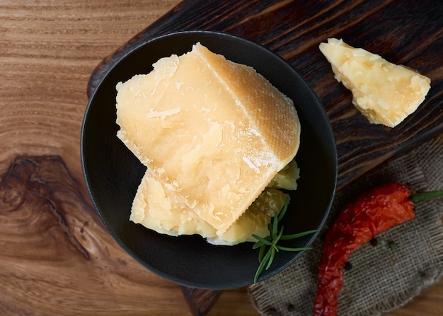Layout of hard cheese on a dark background with spices. pieces of parmesan cheese in a black plate.