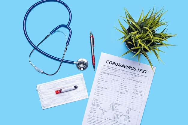 Layout of health and medical care testing for checkup on patients with virus, with stethoscope, plant pot, pen, facemask, test tube and document testing on corona virus, on blue flat lay background