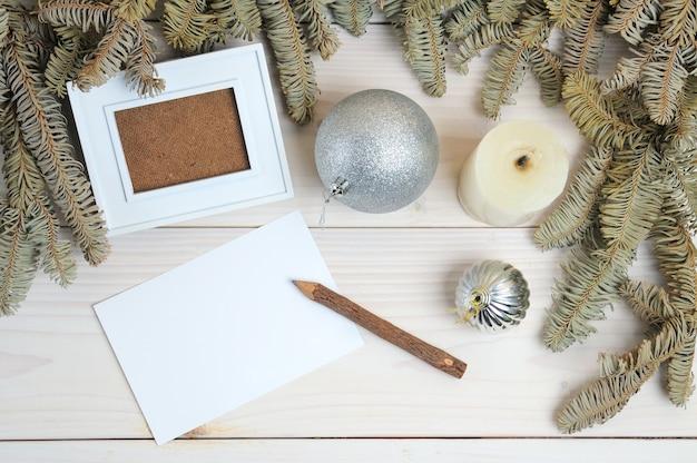 白い木の表面のクリスマスをテーマにしたフォトフレーム、紙、鉛筆のレイアウト