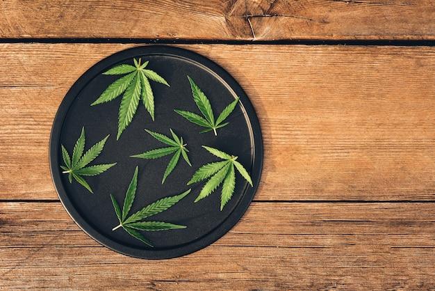 マリファナの美しい葉、丸い黒い皿にさまざまなサイズの大麻のレイアウト