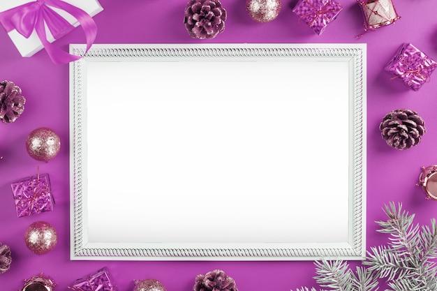 그들의 크리스마스 장식과 분홍색 배경에 여유 공간이있는 인사말 카드의 레이아웃.