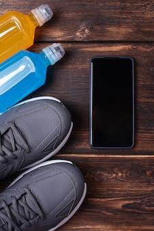 스포츠 훈련 개념, 운동화, 스마트폰, 그리고 짙은 나무 배경에 있는 두 병의 등장성 음료의 레이아웃, 모형, 클로즈업.