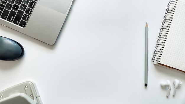 Макет на тему образования или работы на белом фоне с блокнотом, ручкой, ноутбуком, компьютерной мышью, папкой для бумаг, дыроколом, наушниками, карандашами. плоская планировка, верхняя конкуренция