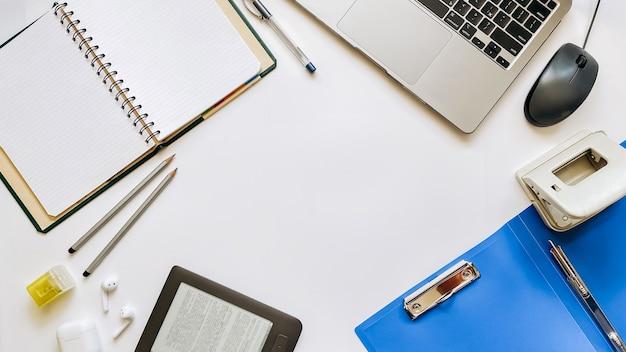 Макет на тему рабочего процесса или образования на белом фоне с блокнотом, ручкой, ноутбуком, компьютерной мышью, планшетом, дыроколом, наушниками, карандашами. плоская планировка, вид сверху.