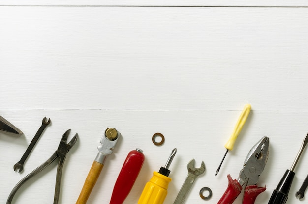 Layout of repair and construction tools on a white wooden background. space for text