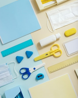 Layout of school supplies, notebooks, pens, pencils, medical mask and hand sanitizer