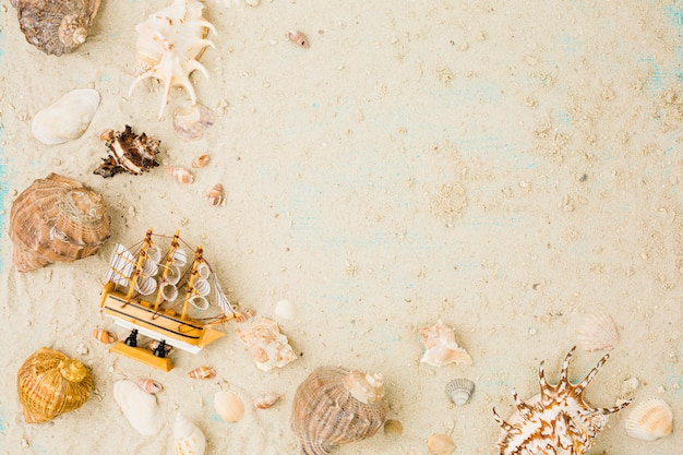 Layout of seashells and toy boat on sand