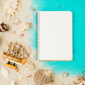 Layout of seashells and toy ship among sand near notebook