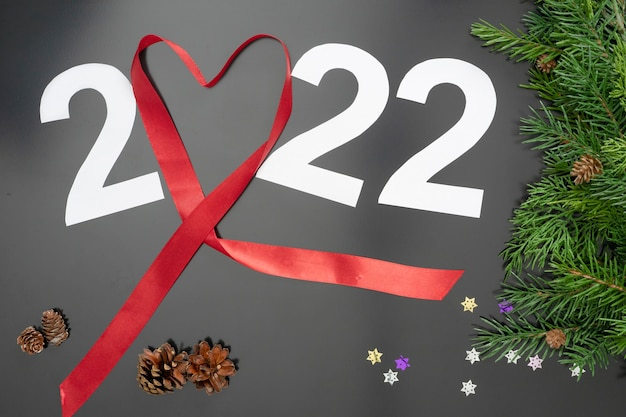 Layout on the theme of the new 2022 with a red ribbon, toys and branches of a christmas tree on a dark background.
