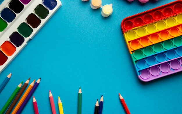 Макет вид сверху детских школьных принадлежностей pop it, акварель, цветные карандаши на синем фоне с местом для текста, цветные школьные принадлежности