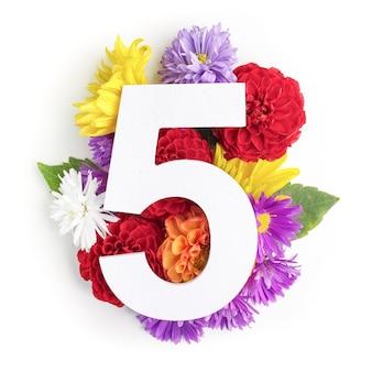 Макет с яркими цветами, листьями и номером пять. плоская планировка. вид сверху.