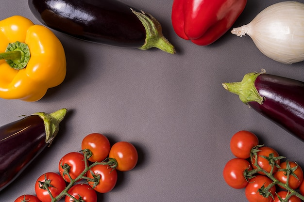 Layout with different vegetables over gray background with copy space.