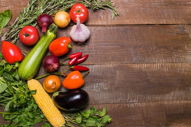 Layout with different vegetables on old wooden table with copy space.