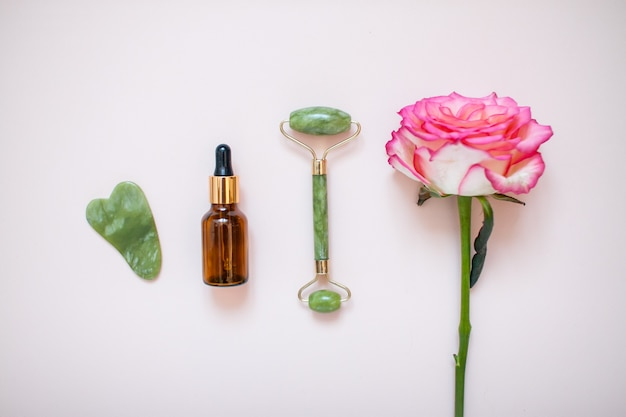 Layout with jade facial massager and beautiful rose on light pink background. high quality photo