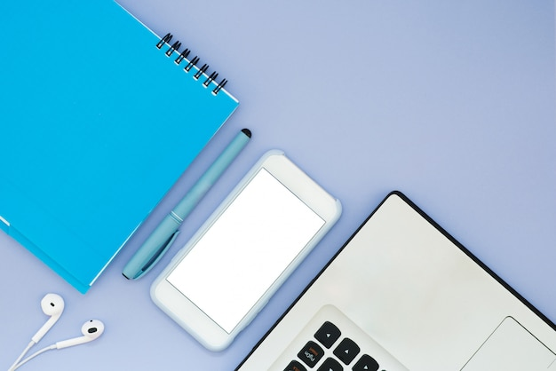 Layout with a laptop, phone, notepad and headphones on a blue background. place for text. flat lay desktop tools layout