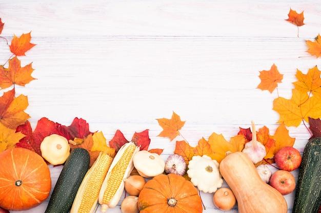 カボチャ、とうもろこし、その他の野菜、紅葉のレイアウト。明るい木の背景の上面図。