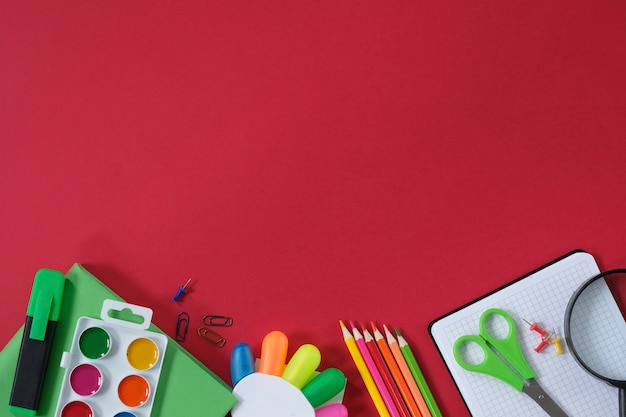 Layout with school supplies and stationery on red background.