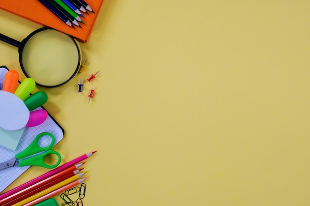 Layout with various school supplies and stationery on yellow background.