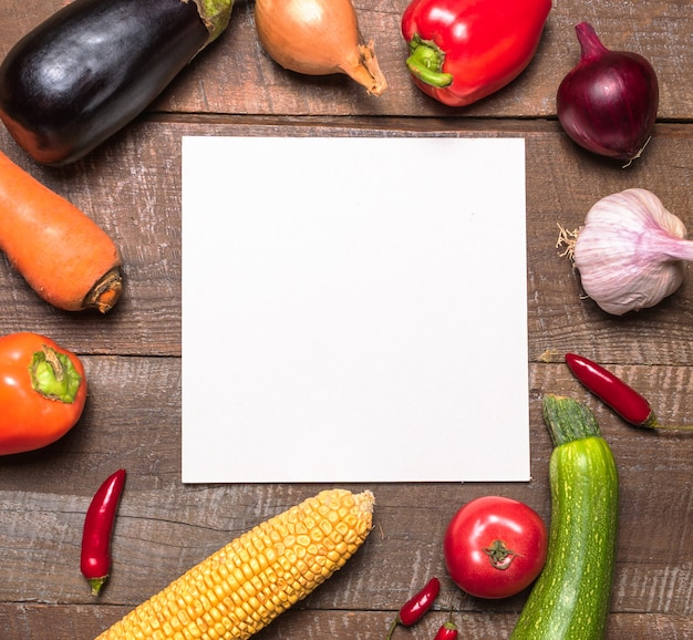 Layout with various vegetables and fruits and white paper card for text .