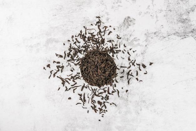 Высушенный чай наливают в белую керамическую чашку на мраморном столе. вид сверху. layout.