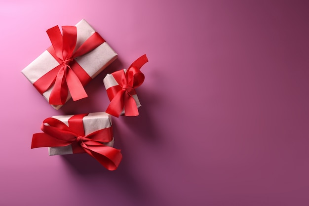 Символы влюбленности поздравительной открытки предпосылки дня валентинки, красное украшение с коробками подарков. вид сверху с копией пространства и текста. плоский layy