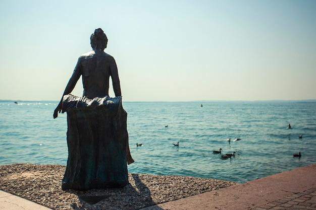 Lazise, italy 16 september 2020: lazise statue near the lake