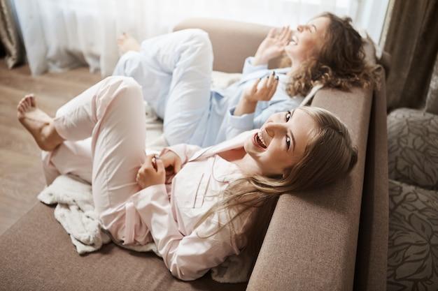 Ленивые люди ничего не делают и наслаждаются отдыхом вместе. съемка под большим углом симпатичных женщин, сидящих на диване в пижаме, громко смеющихся, говорящих о неловких моментах в офисе, проводящих выходные