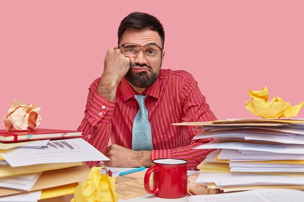 Lazy displeased fatigue male worker keeps fist on cheek, has sleepy look, dressed in formal shirt and tie, works with papers, has mess on workpace