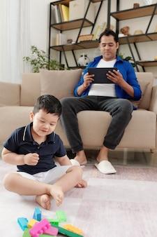 아들이 앞에 있는 바닥에서 다채로운 장난감 블록을 가지고 놀 때 태블릿 컴퓨터로 비디오를 보고 있는 게으른 아버지