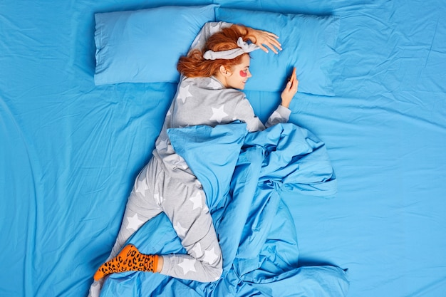 Lazy ginger woman dressed in comfortable nightwear applies hydrogel patches under eyes to reduce wrinkles and puffiness after sleep lying in bed on blue bedclothes uses mobile phone for chatting