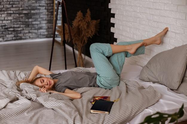 Ленивое доброе утро блондинка лежит на кровати и улыбается