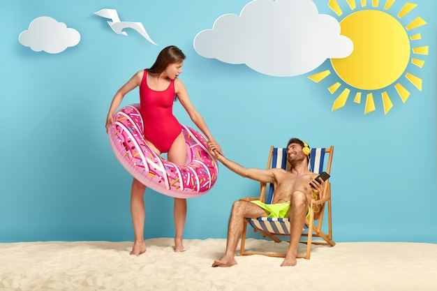 Lazy guy sits at beach chair, enjoys listening pleasant music, stretches hand to girlfriend who stands in pink inflatable swimming ring