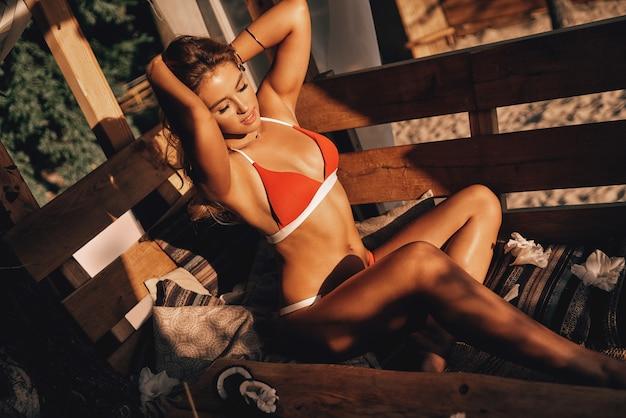 게으른 더운 날. 빨간 비키니를 입은 매력적인 젊은 여성이 머리 뒤로 손을 잡고 야외 해변 오두막에서 휴식을 취하면서 웃고 있는 모습