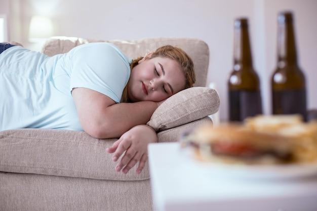Ленивый образ жизни. полная рыжая женщина спит на диване после того, как съела всю нездоровую пищу