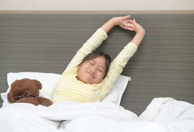 Lazy little girl wakes up and stretching on bed in morning, health care and good morning world concept