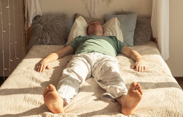 Ленивый мужчина спит или мечтает днем при дневном свете на кровати в спальне.