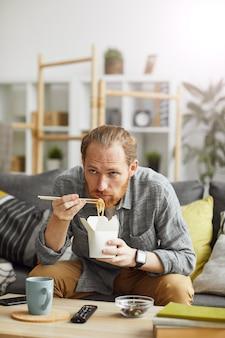 Ленивый мужчина смотрит телевизор у себя дома