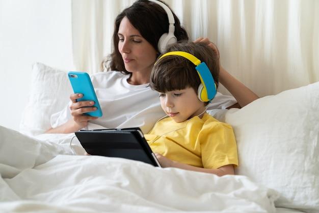게으른 엄마와 아이는 아침에 침대에 누워 전화로 온라인 쇼핑을 하고 태블릿으로 게임을 즐깁니다
