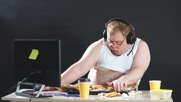 Lazy, plump man in a t-shirt and headphones wanders the web. people like computer games. the concept of addiction