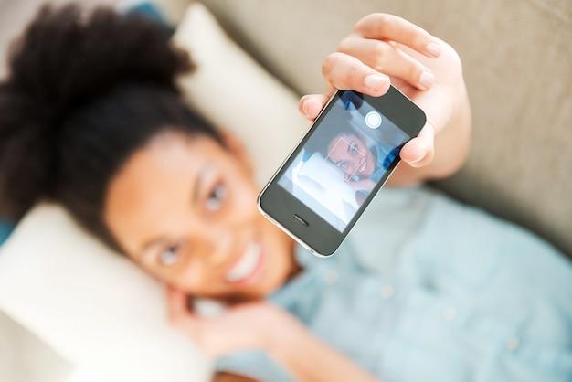 게으른 셀카. 헤드폰을 끼고 집에서 소파에 누워 음악을 듣고 웃고 있는 매력적인 젊은 아프리카 여성의 상위 뷰