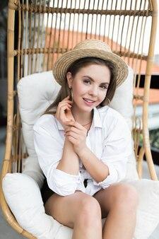 Tempo pigro su una sedia comoda. bella giovane donna che si distende su una sedia grande e comoda sulla terrazza della sua casa all'aperto