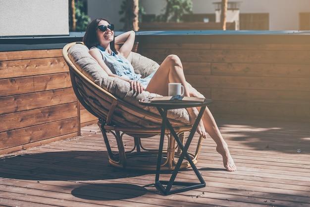 편안한 의자에서 나른한 시간. 야외 집 테라스에 있는 크고 편안한 의자에서 휴식을 취하는 아름다운 젊은 여성