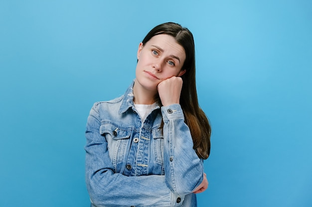 Lazy unhappy woman standing leaning on hand