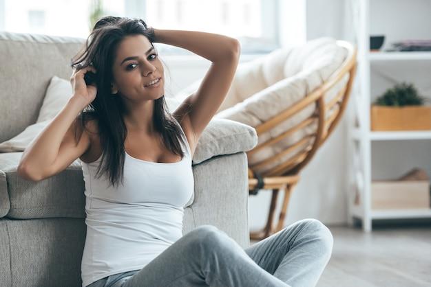 집에서 보내는 나른한 주말. 집에서 바닥에 앉아있는 동안 머리에 손을 잡고 카메라를보고 매력적인 젊은 여자