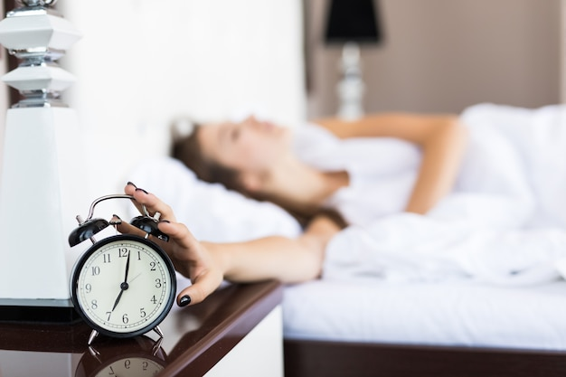 Lazy woman continue to lie after alarm clock ringing in the morning