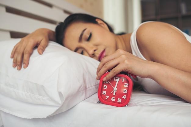 게으른 여자 손을 침대에 알람 시계를 들고