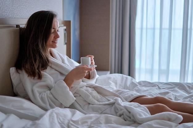 목욕 가운에 게으른 여자가 침대에 누워 호텔 방에서 아늑한 편안한 침실에서 휴식을 취하는 동안 향기로운 커피 컵으로 좋은 아침 아침 식사를 즐기고 있습니다.