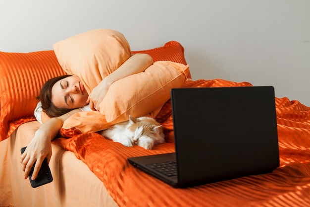 A  lazy woman sleeps in a bed with a laptop on her knees and a sleeping cat nearby.